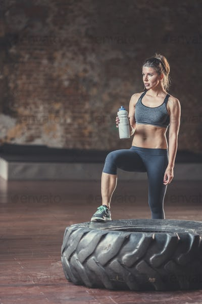 Sports woman with a bottle at workout