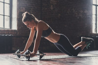 Athletic young girl with dumbbells