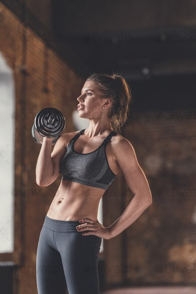 Athletic young girl with dumbbells indoors