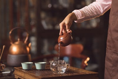 Women's hands pouring tea indoors