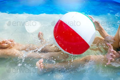 Kids playing at outdoor swimming pool. Little girl and boy play and swim in a home inflated pool