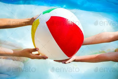 hands of little boy and girl playing with Multi Colored Beach ball in swimming pool