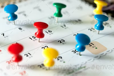 Thumb tack pins on calendar as reminder