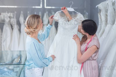 A young seller and customer with a wedding dress