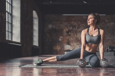 Young sporty girl with dumbbells