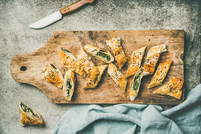 Freshly baked Turkish borek roll cut in slices, flat-lay