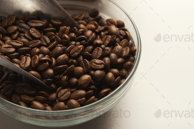 Closeup of bowl with roasted coffee beans on white background