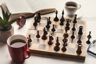 Wooden desk with chess play, book and coffee cup