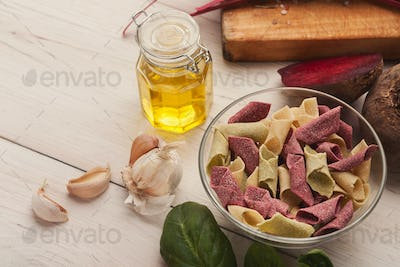 Italian pasta in bowls and laurel leaf on white wood