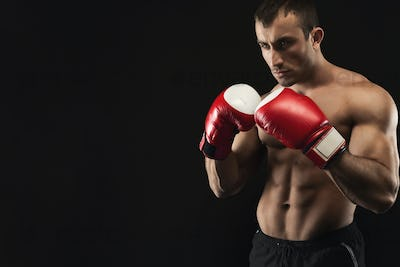 Muscular man in boxing gloves at black background