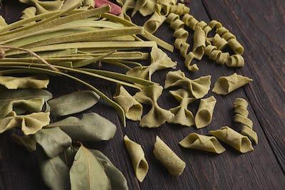 Assorted italian green pasta on wooden background