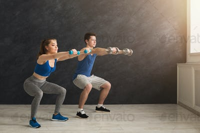 Young couple in sportswear doing squat