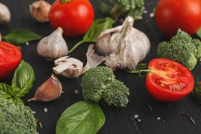 Fresh tomatoes and garlic closeup on dark rustic wood