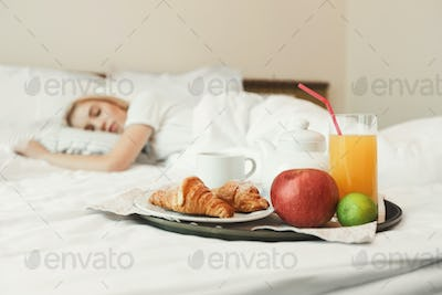 Closeup of breakfast in front of sleeping woman