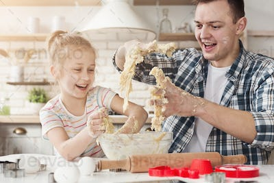 Cute little girl and father kneading dough and smiling