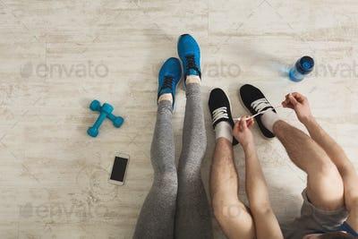 Unrecognizable fitness couple having rest at gym