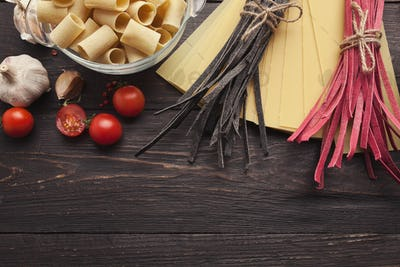 Red italian pasta and cooking ingredients on wooden table