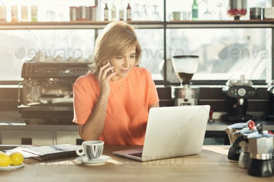 Middle-aged woman barista working on laptop and talking on smartphone