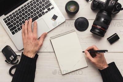 Photographer taking notes while using laptop