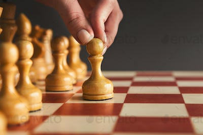 Hand of player chess board game putting white pawn