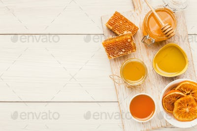 Variety of honey on white wooden planks, top view