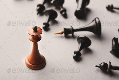White chess queen beats blacks on gray background