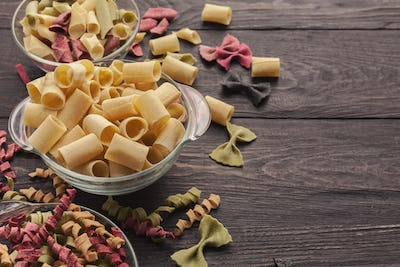 Various colorful pasta in glass bowls on wooden background
