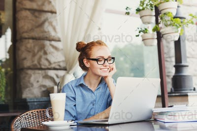 Young redhead female freelancer outdoors working with laptop