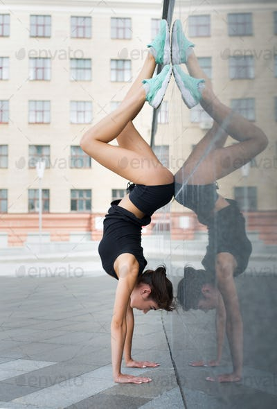 Young woman doing handstand on city street