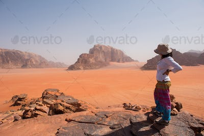 Woman admiring desert landscape on a cliff