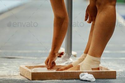 female gymnast rubs chalk on his legs