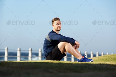 young sports man sitting outside after workout