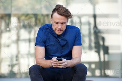 one guy sitting outside in city with mobile phone