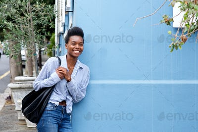 smiling young woman leaning against wall with bag