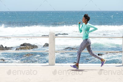 young african american woman running by the sea