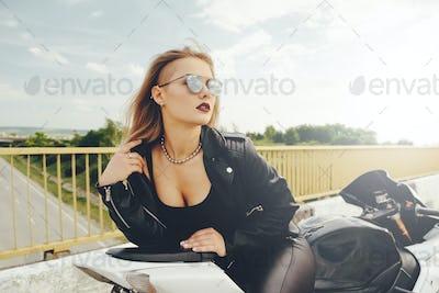 Beautiful woman posing with sunglasses on a motorbike