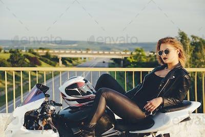 Beautiful woman biker laying on a bike relaxing