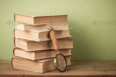 Stack of old books and magnifying glass on wooden table