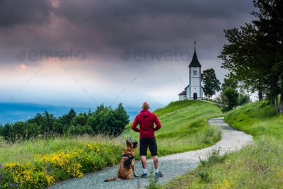 Man with dog looking at  Church of  St. Primus and Felician, Jam