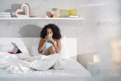 Woman Drinking Coffee Watching Movie In Bed on Sunday
