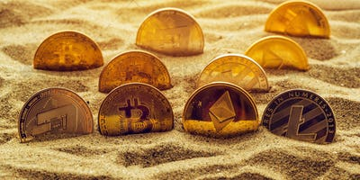 Cryptocurrency coins in sand