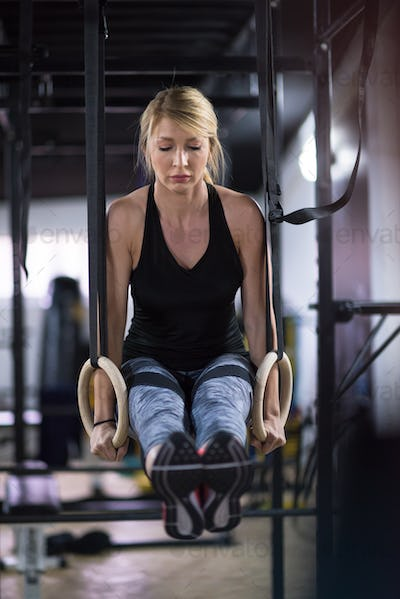 woman working out pull ups with gymnastic rings