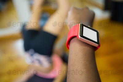 Womans hand using smart watch while workout in fitness studio
