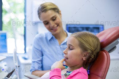 Young patient looking in the mirror at dental clinic
