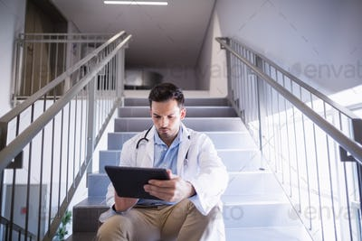 Doctor sitting on staircase using digital tablet