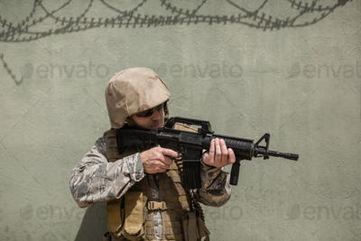 Military soldier aiming with a rifle against concrete wall
