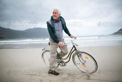 Senior man riding bicycle on the beach