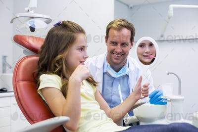 Smiling young patient looking in the mirror in dental clinic