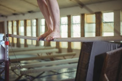 Female gymnast practicing gymnastics on the horizontal bar