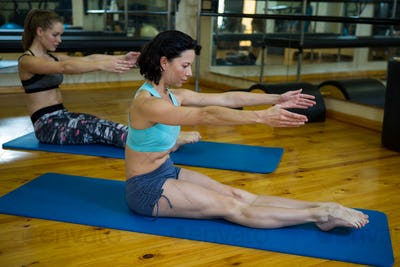 Fit women performing stretching exercise